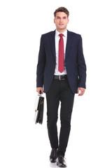 Smiling young business man walking