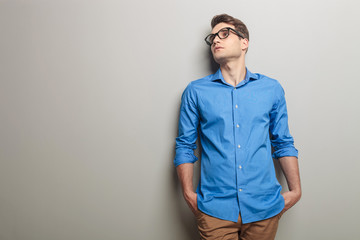 Young casual man leaning his head on a grey wall.