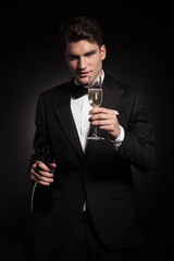 elegant man holding a bottle and a glass of champagne.