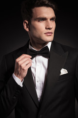 Handsome young elegant man fixing his bowtie.