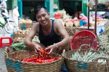 Asian man on street market smile sell red chilly pepper