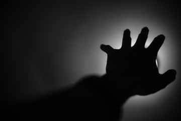 Silhouette of hand reaching to light, Help me concept