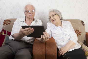 Happy old couple using a modern tablet - technology