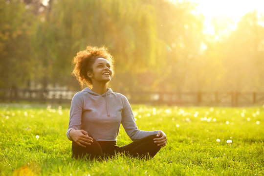 Happy young woman sitting in yoga position