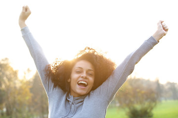 Cheerful young black woman smiling with arms raised