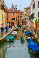Tourists and the rowers on a rainy day in Venice