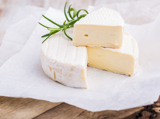 Traditional Camembert with rosemary on white paper