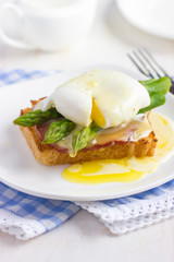 Eggs Benedict with hollandaise sauce on toast with  bacon and as