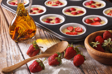 cooking berry muffins with fresh strawberries