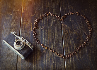 The vintage camera and coffee heart on a wooden background