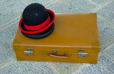 hat and suitcase of a street actor