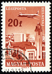 Flying plane above the Helsinki on post stamp