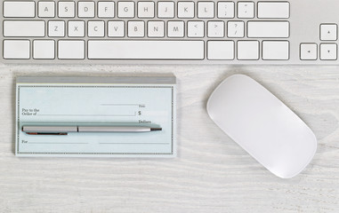Blank checkbook on white desktop with pen and mouse