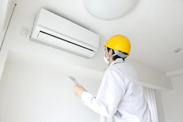 エアコンを点検する作業員