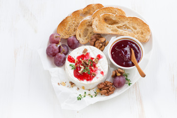 camembert with berry jam and toast on a white wooden background