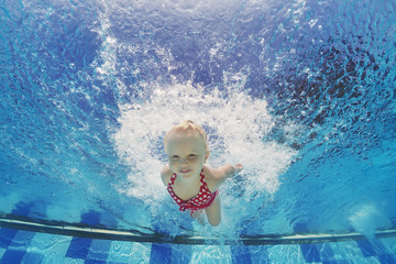 Baby girl swimming and diving in pool with fun - jumping deep down underwater with splashes Active lifestyle, water sports activity and exercising with parents during summer family vacation with child