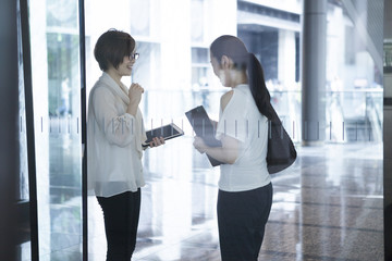 Women have a chatting in the glass-walled building