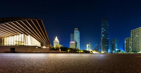 Fotomurales - Empty asphalt road and modern skyline at night