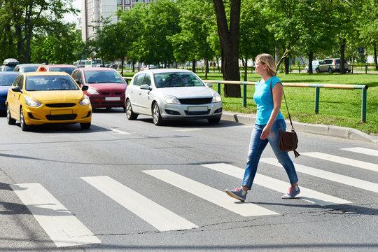 Woman crossing street at pedestrian crossing