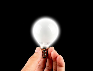 Holding light bulb with black background