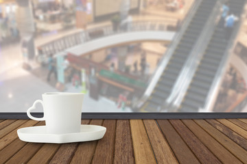 Coffee cup on wood table with fade out of shopping mall as backg