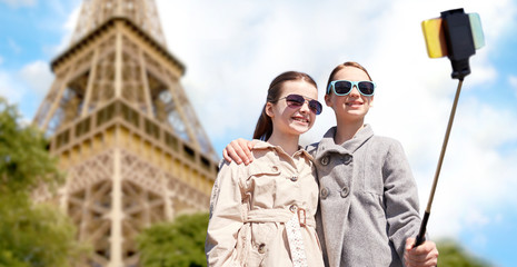 girls with smartphone selfie stick at eiffel tower