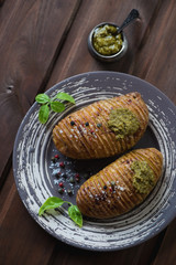 Swedish hasselback potatoes served with basil pesto, top view