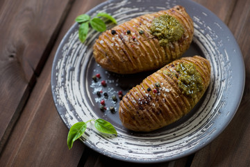 Baked hasselback potatoes served with basil pesto sauce