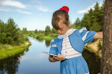 Над рекой/Девочка на берегу реки с планшетом.