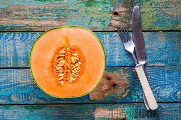 half ripe melon on a rustic background with knife and fork