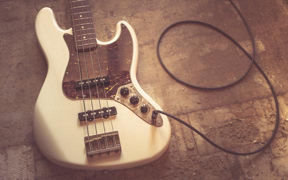 old vintage electric bass guitar on basement floor