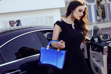 woman in elegant dress with bag, posing beside a luxurious auto
