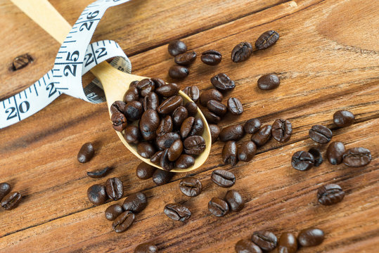 Coffee bean on wooden spoon, tape measure on wooden background