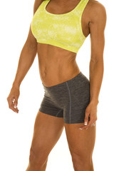 woman gray shorts and green sports bra body side