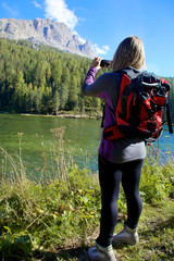 Woman in the mountain taking picture of beautiful landscape