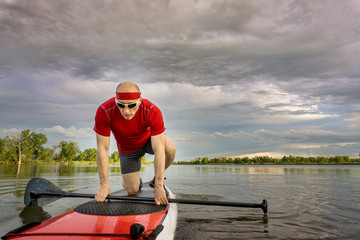 male stand up paddler on lake