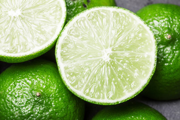 Fresh limes cut in half on black surface