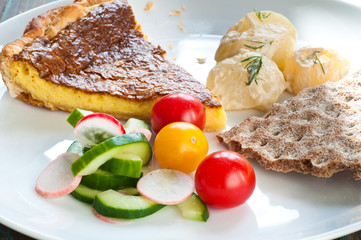 Slice of Swedish Vasterbotten pie served with new potatoes, crispbread and a salad of cucumber, tomato and radish.