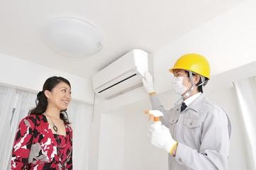 エアコンについて作業員の説明を受けている女性