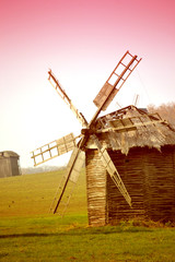 ancient windmill on the field with pink filter