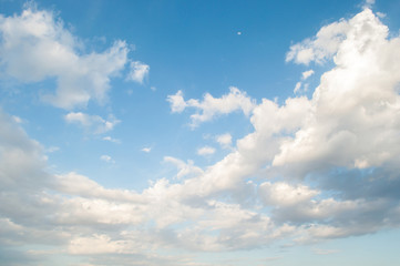 Blue sky with clouds and a little moon