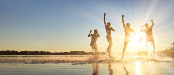 Glückliche junge Menschen laufen und springen am See beim Sonnenuntergang Wall mural