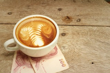 Hot latte coffee with Thailand baht banknotes
