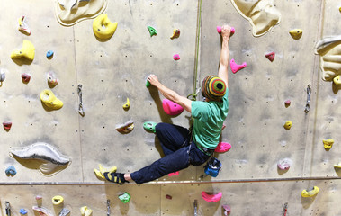 Mann klettert in einer Indoor Kletterhalle // climbing indoor