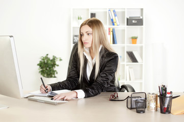 A woman in her mid thirties sits at desk in front of computer screen.
