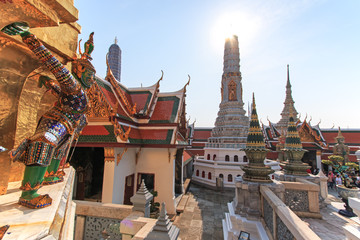 Bangkok, Thailand - April 14,2015: Statue of Yaksa on guard at the Temple of the Emerald Buddha and tourists on background