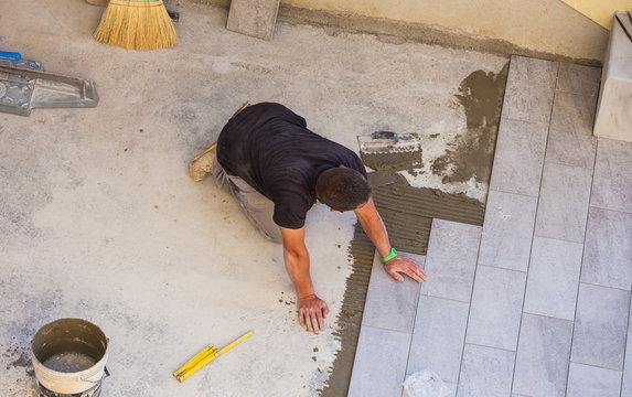 Worker Installing ceramic floor tiles