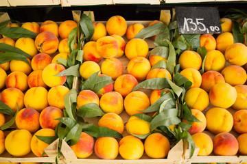 Fresh peaches arranged in row on farmers market