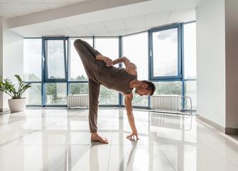 Man training yoga at the gym