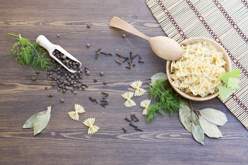 Pasta with herbs and spices on dark wooden table